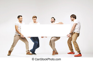 Casual clothed guys carrying huge billboard
