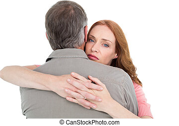 Casual couple hugging each other on white background