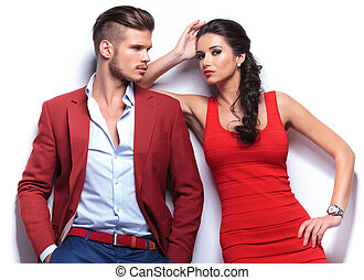 casual couple leaning against a white wall, man with hands...