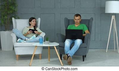 Casual couple networking with digital devices at home