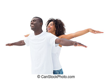 Casual couple standing with arms outstretched on white...