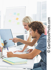 Casual couple using computer in office