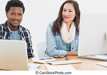 Casual couple using computers in office