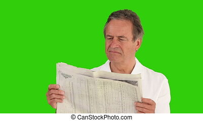 Casual elderly man reading a newspaper against a green ...