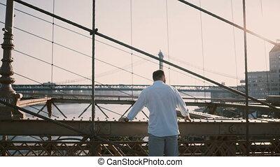 Casual European businessman standing at Brooklyn Bridge using smart watch bracelet, then turning back from camera 4K.