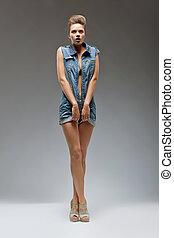 Casual fashion girl wearing blue jeans posing in studio