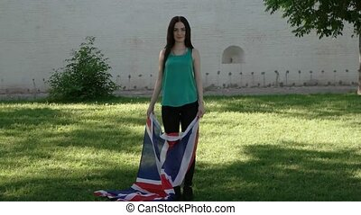 Casual girl having fun with GB flag. Women play with Union Jack.