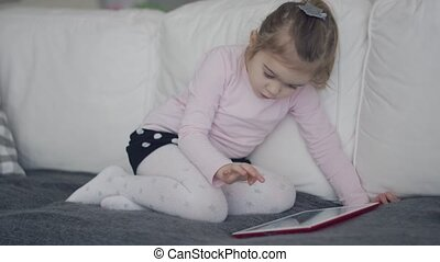 Casual girl using tablet on sofa