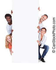 Happy Casual Group Of People Holding Placard Over White Background