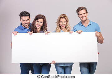 casual group of young people holding a big blank board