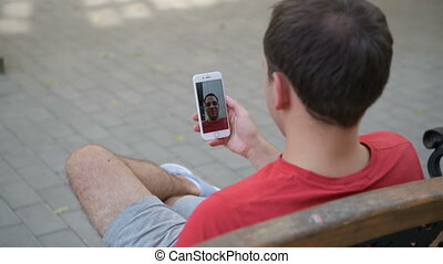 Casual happy man using a smartphone recording video message...