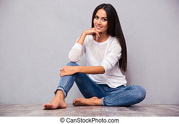 Casual happy woman sitting on the floor
