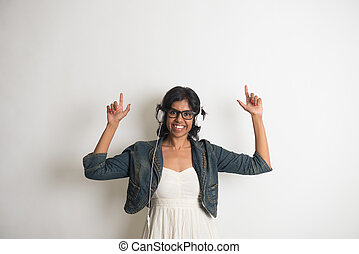 casual indian female listening to music with grey background