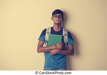 casual indian male student with book
