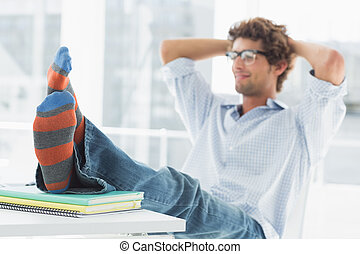 casual, joven, con, piernas, en el escritorio, en, oficina