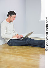 Casual laughing man leaning against wall using laptop in...