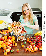 Casual long-haired girl cooking fruit salad