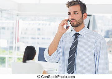 Casual male artist using mobile phone with colleague in the background at a bright office