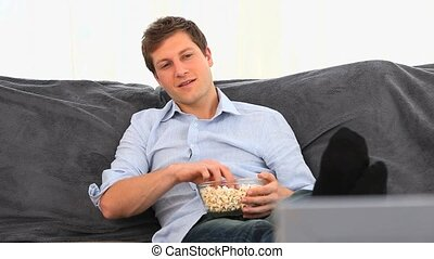 Casual man eating popcorn in his living room