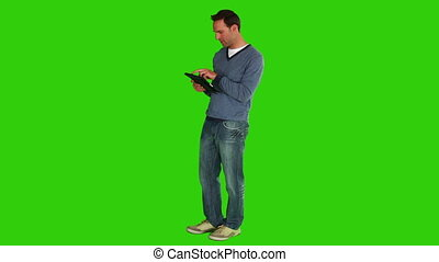 Chromakey footage of a casual man holding a touch pad