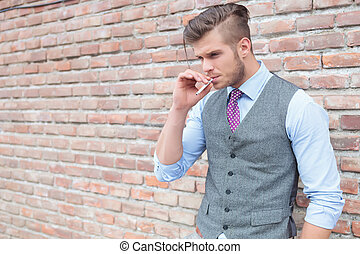 casual man holds cigarette in mouth outdoor - casual young...
