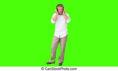 Casual man in shirt listening to music with headphones
