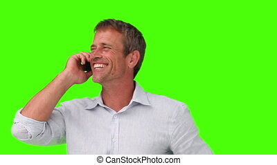 Casual man laughing a lot while he is talking on the phone