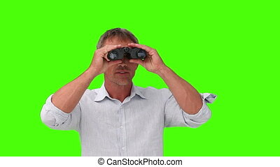 Casual man looking at the landscape with a pair of binoculars