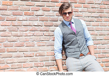 casual man looking at you with his hand in pocket