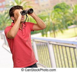 casual man looking into binocular
