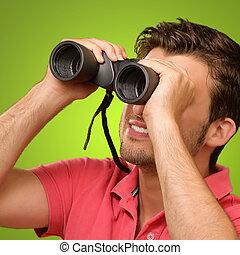 casual man looking into binocular isolated on green...
