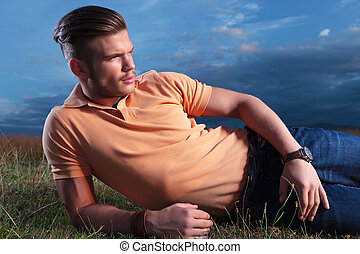 casual man looks away while in grass