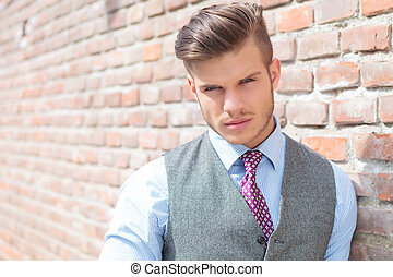 casual man next to a brick wall