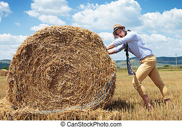 casual man outdoor looks at you and pushes haystack