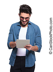 casual man reading something on a computer tablet.