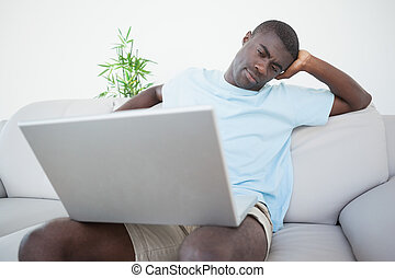Casual man sitting on sofa using laptop