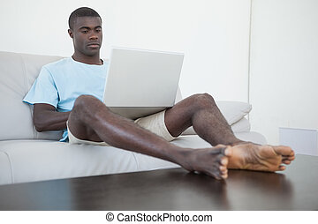 Casual man sitting on sofa using laptop with feet up