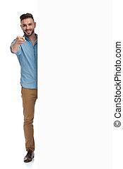 casual man standing behind billboard pointing forward