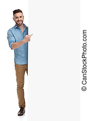 casual man standing behind billboard pointing towards it