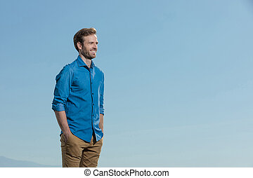 casual man standing relaxed with hands in pocket