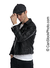casual man standing with hand in pocket fixing hat tough