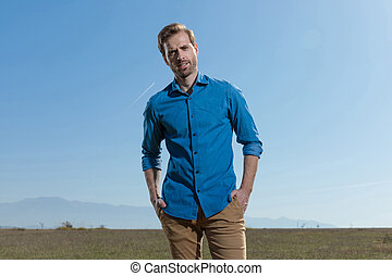 casual man standing with hands in pocket relaxed