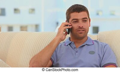 Casual man taking a phone call on his sofa