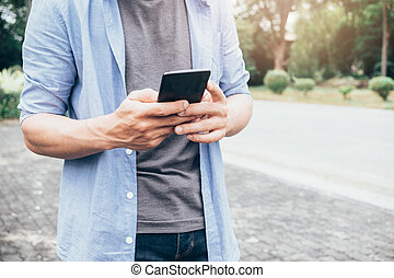 Casual man using a smart phone texting messages.