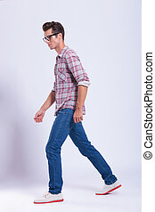 full length picture of a casual young man walking and looking away from the camera. on gray background