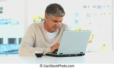 Casual man with a laptop looking at the camera
