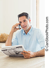 Casual man with newspaper using cellphone in kitchen