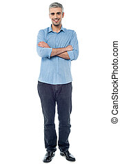 Full length picture of a casual senior man, arms folded