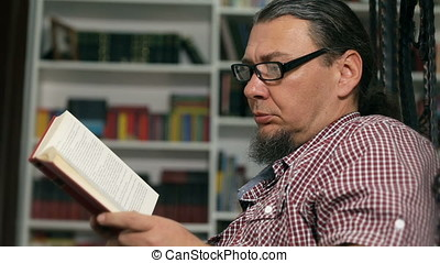 Casual middle aged man reading a book, bookshelves on background