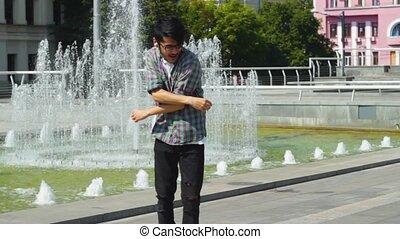 Casual modern man in headphones dancing on street - Modern...